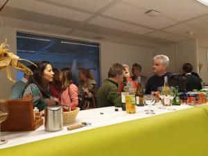 foto mensen staande aan een bar vol flessen wijn geanimeerd pratend