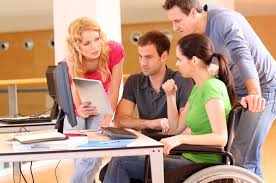 Mensen achter een tafel met PC. 1 vrouw in een rolstoel