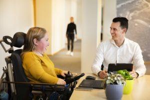 Twee mensen aan een Tafel. Een vrouw in een rolstoel en een man achter een laptop