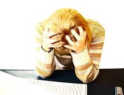 Vrouw met de handen in het haar achter een PC