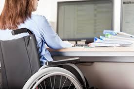 Vrouw in rolstoel achter een bureau met een computer